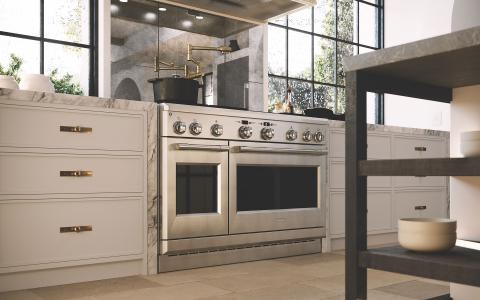 white kitchen with stainless steel range and reflective backsplash
