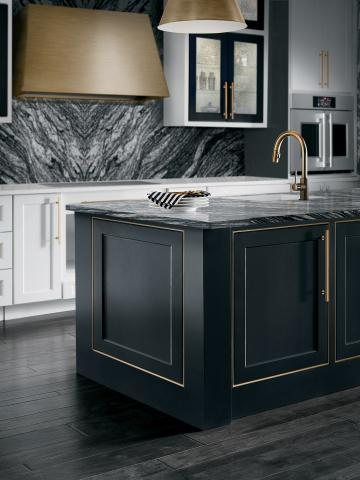 black kitchen island with brass range hood and marble backsplash