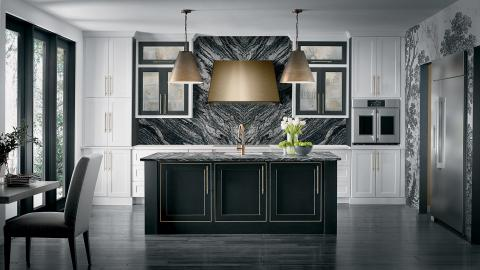 white kitchen with black island and brass lighting and range hood