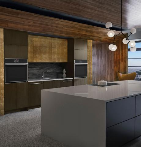 brown and gold kitchen with white waterfall island