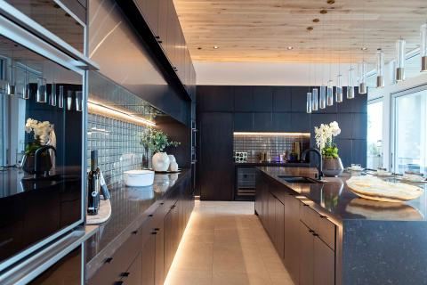 black kitchen with glass tile backsplash and large island