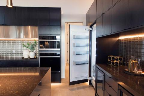 black kitchen with glass tile backsplash and glass front wall ovens