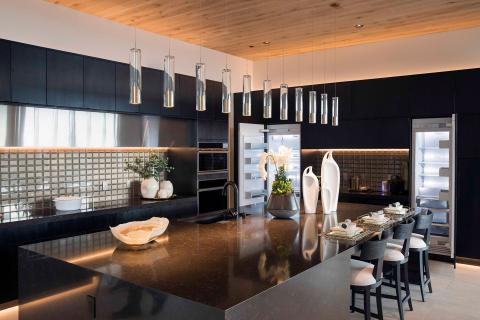 black kitchen island with waterfall edge and series of glass pendant lights